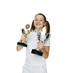 Proud young girl holding two trophies