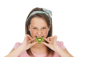 Young girl biting into a slice of kiwifruit