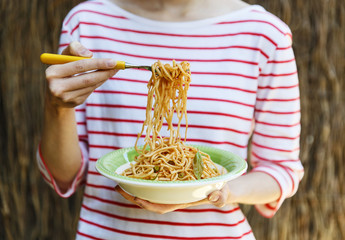 Female hands holding plate with pasta