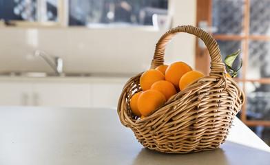 Kitchen tabletop and basket of oranges