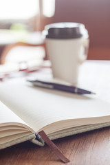 Open notebook with pen and coffee cup