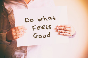 "woman holding board with the phrase ""do what feels good"" written"