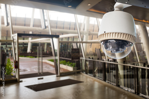 CCTV Camera operating in front of glass door - 69244342