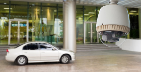 CCTV Camera Operating on glass building with car
