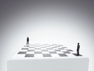 Two tiny figures standing on a chess board