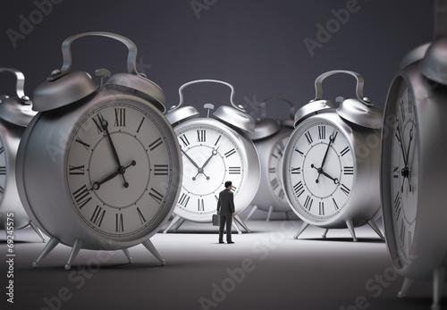 Leinwandbild Motiv Tiny businessman with alarm clocks