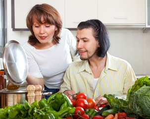 Brunette beautiful housewife with man cooking with fresh vegetab