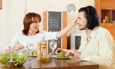 middle aged couple eating salad with water at home.