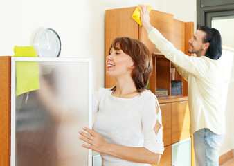 middle-aged couple wiping the dust at home