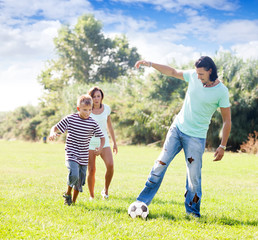 Happy parents with child playing with  ball