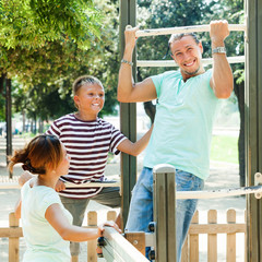 man with family training on chin-up bar