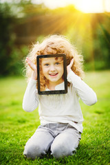 Little girl sitting on the grass and holding tablet pc.