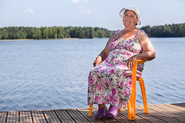 Smiling aged woman sitting on wooden pier at lake, copyspace