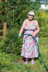 Pension age woman pouring trees at country residence