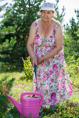 Senior woman pouring water from hose into watering can in garden