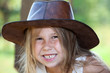Toothy smile of young pretty girl in cowboy hat, facial portrait