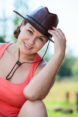 Cheerful smiling Caucasian woman in cowboy hat