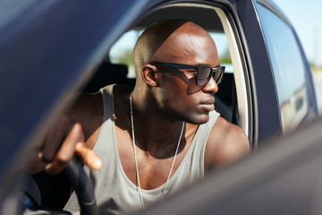 Stylish african young man in his car
