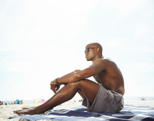 Shirtless young man sitting on beach looking away