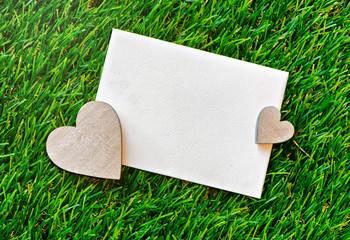 Romantic valentines card on green grass and hearts