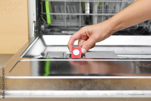 Leinwanddruck Bild Woman putting tablet in dishwasher detergent box