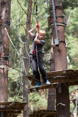 Junge am Seil im Kletterwald