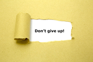 Don't Give Up! appearing behind torn brown paper