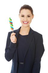 Beautiful businesswoman with lollipop