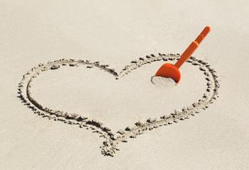 Cuore sulla sabbia con paletta