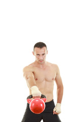 athletic man holding and lifting up red kettlebell weight