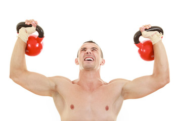 athletic half naked man holding and lifting red kettlebells weig