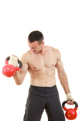 athletic man holding and lifting up red kettlebells weights one