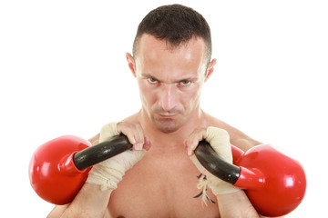 concentrated athletic man holding red kettlebells weights lifted