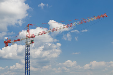 construction crane on blue cloudy sky background