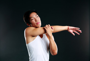 Pensive asian man stretching hands on black background
