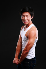 Happy fit asian man posing on black background