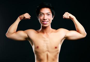 Handsome fit asian man on black background