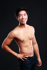 Portrait of a cheerful asian man standing on black background