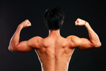 fitness muscled man back on black background