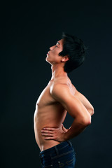 Portrait of asian man stretching on black background