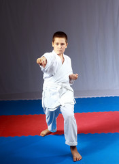 On the mat, the boy in karategi is beating blow karate arm