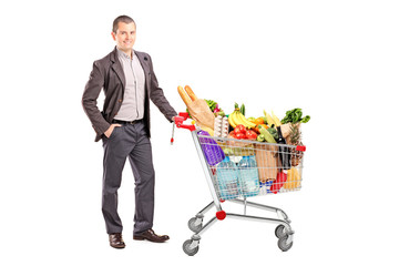 Handsome man with shopping cart full of groceries