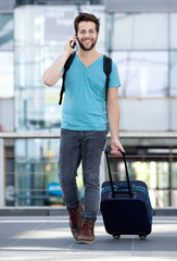 Young man talking on mobile phone with bag