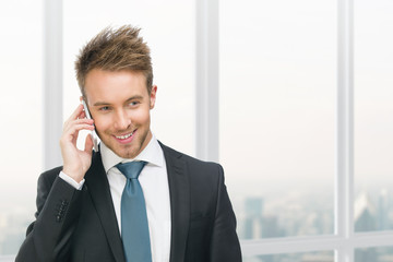 Half-length portrait of businessman speaking on cell phone