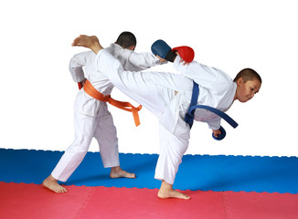 Sportsmen are doing paired exercises on the red and blue mat
