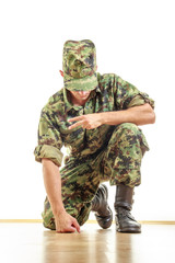 soldier in camouflage uniform and hat kneeling on the floor and