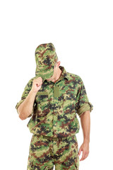 soldier with hidden face in green camouflage uniform covers face
