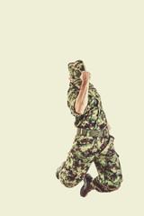 soldier with hidden face in green camouflage uniform jumping
