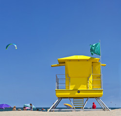 Yellow Life Guard Tower at the beach with people and kite surfer