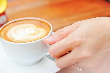 Woman hand with a white cup coffee